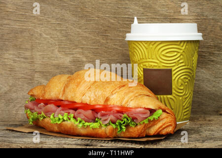 Big croissant with green salad, tomatoes and pork meat near paper coffee cup on old wooden background - Stock Photo