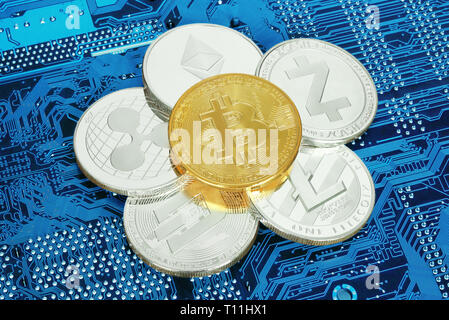Cryptocurrency coins on circuit board background close-up - Stock Photo