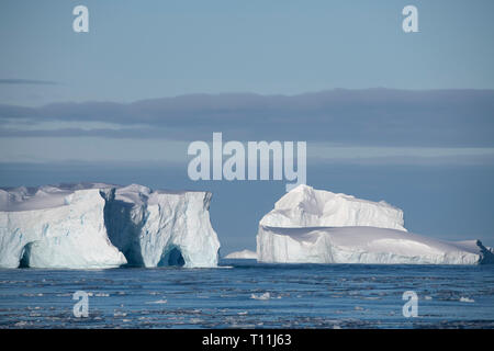 Antarctica, below the Antarctic Circle. Ice filled bay in the Bellingshausen Sea in Crystal Sound. Tabular iceberg. - Stock Photo