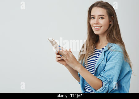 Studio shot charming feminine modern young 25s european woman long healthy hair holding digital tablet turning carefree delighted smile camera - Stock Photo
