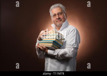 Scientific thinker, philosophy, elderly gray-haired man in a white shirt with a books, with studio light, isolated - Stock Photo