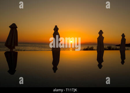 Greece, Zakynthos.  Pool umbrellas reflected in an infinity pool at sunrise. - Stock Photo