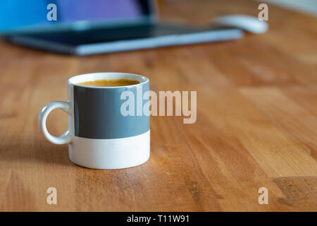 cup of espresso in front of a notebook on a workdesk - Stock Photo