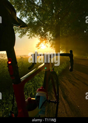 Road bike in the first sunbeams of the day at sunrise - Stock Photo