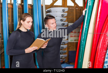 Young man and woman dressed surfing suits checking a surfboards on racks in surf club. Focus on both persons - Stock Photo
