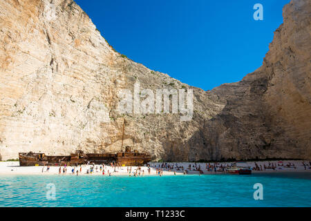 Greece, Zakynthos, Navagio. Famous shipwreck on a secluded beach with tourists. - Stock Photo