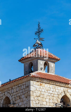 Couple of storks making a nest on the steeple of a church. Sunny day and blue sky. - Stock Photo
