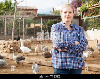 Portrait of smiling and confident young female farmer on poultry yard on background with domestic fowl - Stock Photo