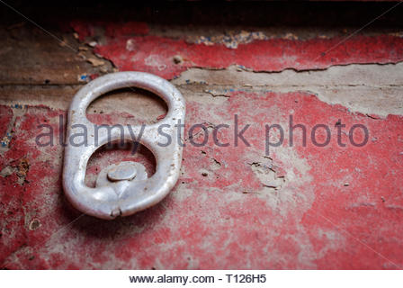 Discarded soda tab left behind on red painted wood that is in disrepair. - Stock Photo