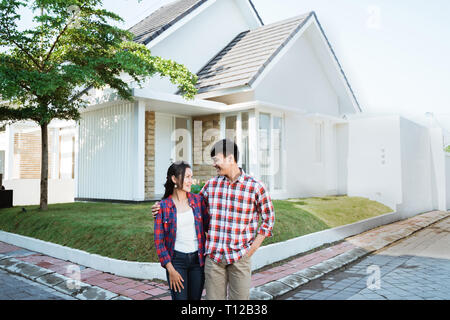asian couple standing in front of their new house - Stock Photo