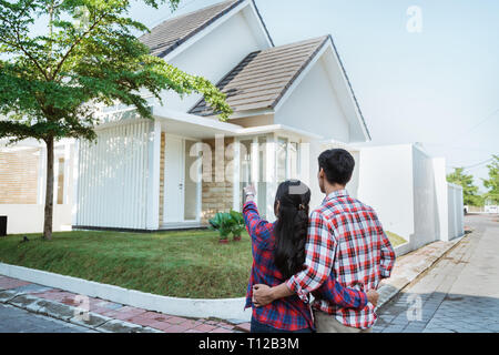 young couple standing in front of their new house - Stock Photo