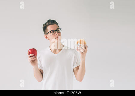 Bearded man in a white shirt on a light background holding a hamburger and an apple Man makes the choice between fast and healthy food. Tasty or usefu - Stock Photo