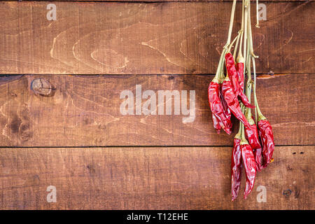Red chili peppers hangs on a wooden wall to dry. Close-up view with space for text. - Stock Photo
