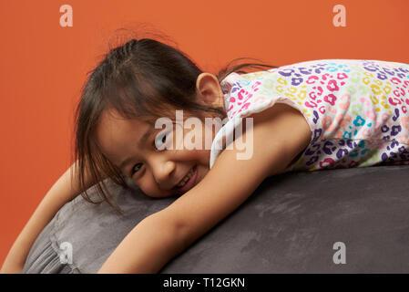 Asian kid relaxing on a beanbag. Filipina kid. - Stock Photo