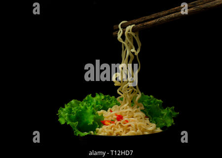 bowl of noodles with vegetables isolated on black,Dried chinese noodle with crispy fried pork levitate in mid air isolated on black background. - Stock Photo