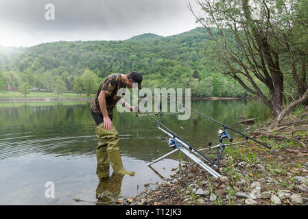 Fishing adventures, carp fishing. Fisherman with green rubber boots - Stock Photo