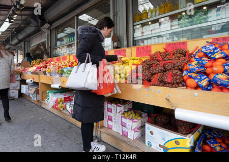 A young Chinese American woman shops for fruits & vegetables on a winter afternoon. In Chinatown, Flushing, Queens, New York City. - Stock Photo