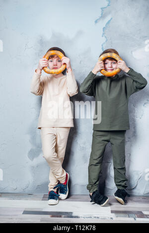 Little twin boys playing and dreaming of becoming a spaceman. Portrait of funny kids with bagels on gray wall - Stock Photo