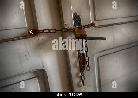 Old metal padlock on a wooden door. - Stock Photo