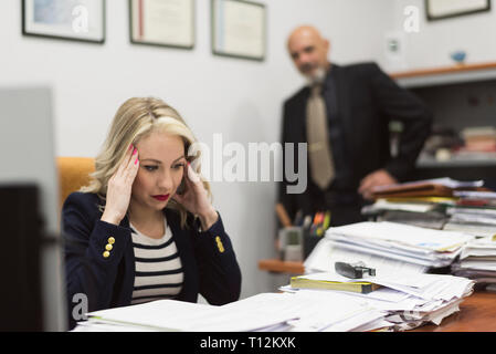 Female office worker stressed before a large load of documents and office work - Stock Photo