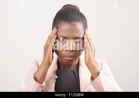 Woman having a terrible headache and keeping hands on head while frowning - Stock Photo