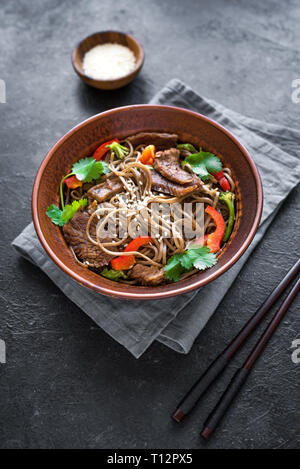 Stir fry with soba noodles, beef and vegetables. Asian healthy food, stir fried meal in bowl on black background. - Stock Photo