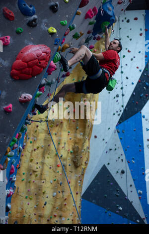 A rock climbing instructor climbs an indoor climbing wall. - Stock Photo
