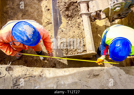 Workers are using metal measure tape, meter to check measurement in square trench. - Stock Photo