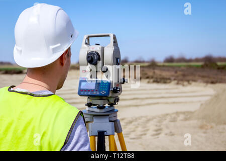 Surveyor engineer is measuring level on construction site. Surveyors ensure precise measurements before undertaking large construction projects. - Stock Photo