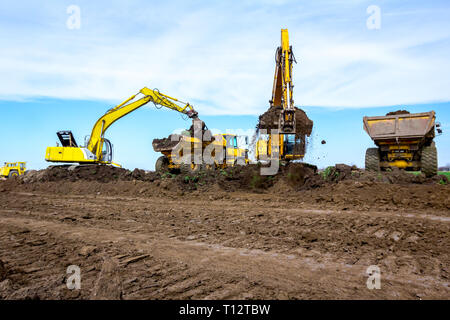 Big excavators are filling two dumper trucks with soil at construction site, project in progress. - Stock Photo