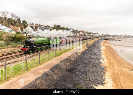 Steam special train pulled by B1 class locomotive 61306 Mayflower steaming alongside the Thames Estuary at Chalkwell, Essex, Southend. Beach seawall - Stock Photo