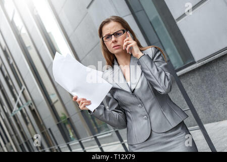 Young businesswoman wearing eyeglasses standing on the city street holding documents talking on smartphone concerned - Stock Photo
