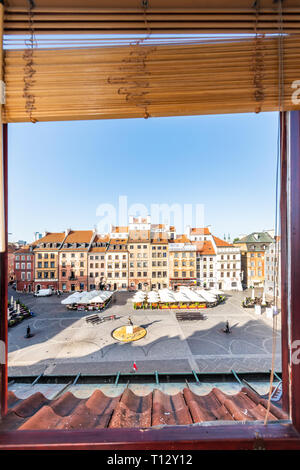 Warsaw, Poland - August 22, 2018: Historic vertical cityscape with view through open glass window of colorful architecture buildings in old town marke - Stock Photo