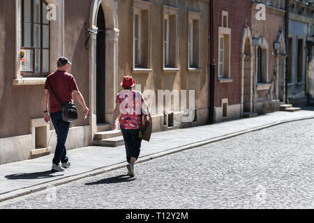 Warsaw, Poland - August 22, 2018: Old town cobblestone street people tourists back walking on summer day cobbled road - Stock Photo