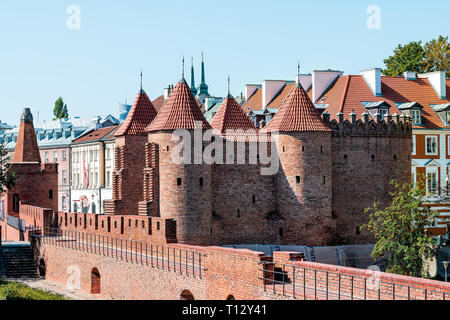 Warsaw, Poland - August 22, 2018: Famous Barbican old town historic cobblestone street in capital city during sunny summer day and red orange brick wa - Stock Photo