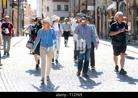 Warsaw, Poland - August 22, 2018: Famous old town historic street alley in capital city during sunny summer day crowd of people tour guide walking - Stock Photo