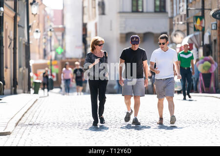 Warsaw, Poland - August 22, 2018: Old town cobblestone street people tourists family walking on summer day cobbled road - Stock Photo