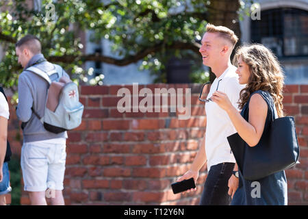 Warsaw, Poland - August 22, 2018: Old town street during summer day and brick fort wall with tourists - Stock Photo