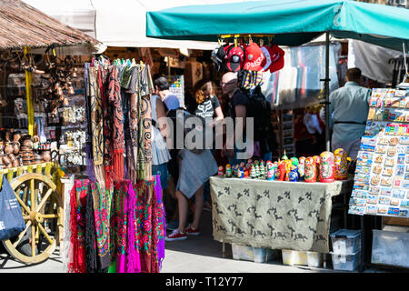 Warsaw, Poland - August 22, 2018: Many summer souvenirs colorful vibrant colors hanging scarves on display in shopping street market - Stock Photo