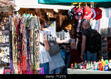 Warsaw, Poland - August 22, 2018: Many summer souvenirs colorful vibrant colors hanging scarves and people in background on display in shopping street - Stock Photo