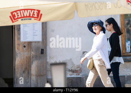 Warsaw, Poland - August 22, 2018: Asian tourists walking in old town on street during sunny summer day by restaurant - Stock Photo