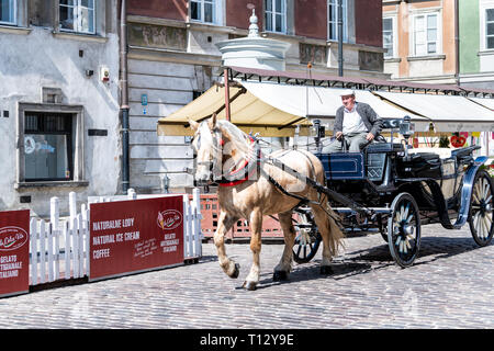 Warsaw, Poland - August 22, 2018: Historic buildings and horse carriage tour in old town during day and guide man - Stock Photo