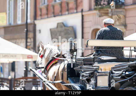 Warsaw, Poland - August 22, 2018: Historic buildings and back of horse carriage tour in old town during day and guide man - Stock Photo