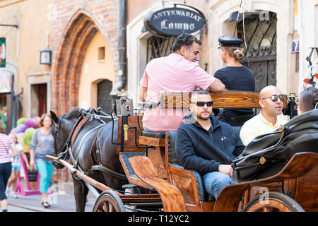 Warsaw, Poland - August 22, 2018: Historic buildings and horse carriage tour sitting in old town during day and guide man - Stock Photo