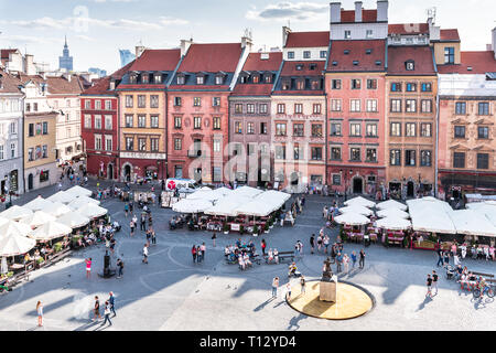 Warsaw, Poland - August 22, 2018: Cityscape with high angle view of architecture rooftop buildings and sky in old town market square in evening with m - Stock Photo