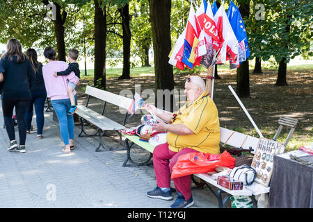 Warsaw, Poland - August 23, 2018: People woman vendor selling souvenirs Polish European Union flags on bench in summer Saxon Gardens Park - Stock Photo