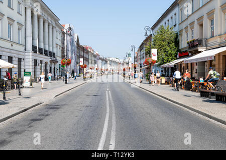 Warsaw, Poland - August 23, 2018: Old town street in capital city during sunny summer day Krakowskie Przedmiescie and row of lanterns architecture - Stock Photo