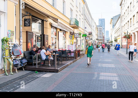 Warsaw, Poland - August 23, 2018: Old town Chmielna cobblestone street sidewalk during sunny summer day architecture with chocolatier store shops - Stock Photo