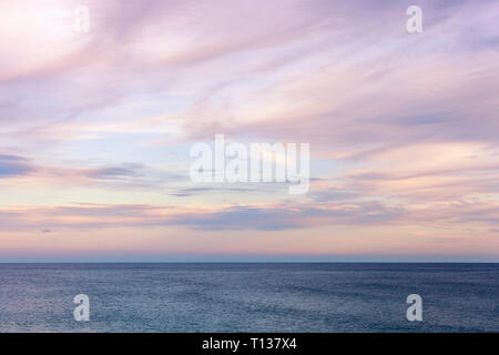 Gorgeous dusk seascape cloudscape rolling over open water. - Stock Photo