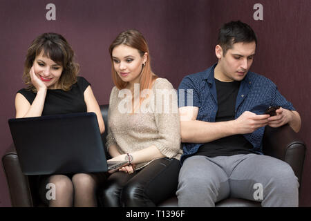 The man is bored looking into the phone and the girls with interest are watching a movie on the laptop. - Stock Photo